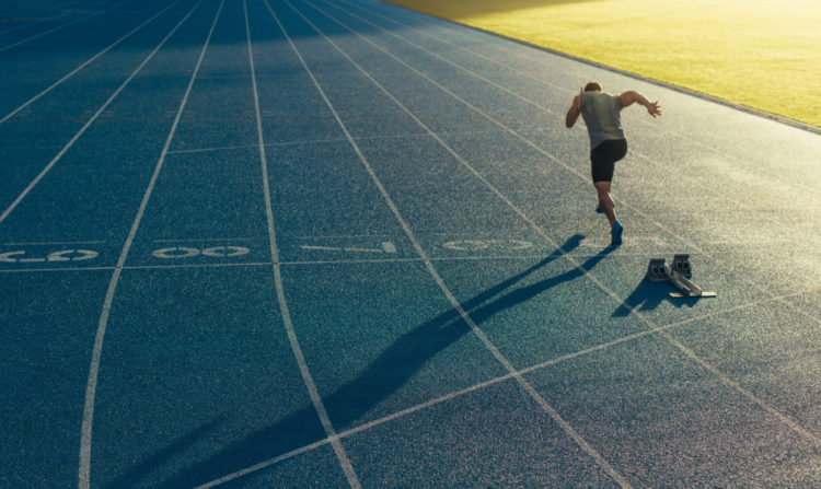 Athlete running on an all-weather running track alone.